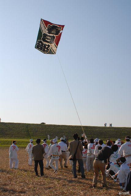 空に舞い上がる大凧と大勢の引手